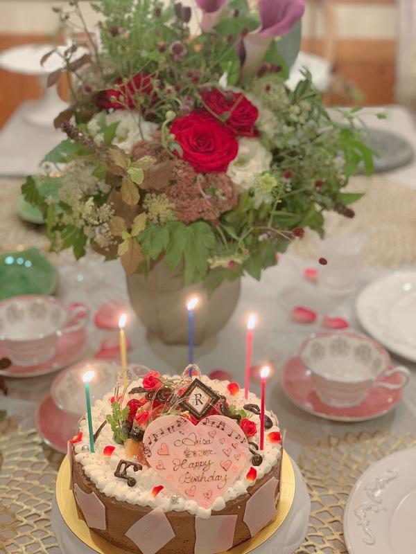 可愛いバースデーケーキと花のあるテーブル
